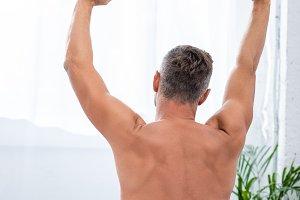 rear view of shirtless man stretchin