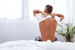 rear view of man putting on white t-
