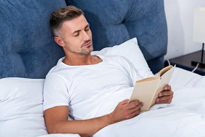 adult man reading book while laying