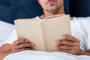 cropped image of man reading book wh
