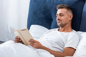 smiling man reading book while layin