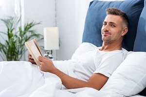 happy man reading book while laying