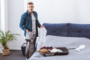 serious male man packing luggage in
