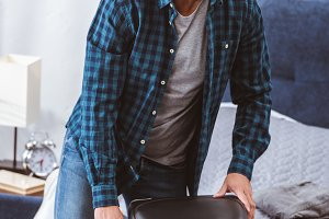 man packing travel bag and looking a
