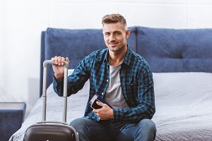 happy male traveler sitting on bed w