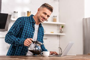 handsome smiling man pouring coffee