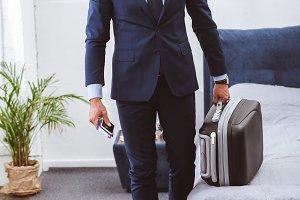 handsome businessman holding suitcas