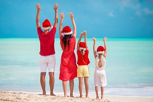 Happy family in red Santa hats on a