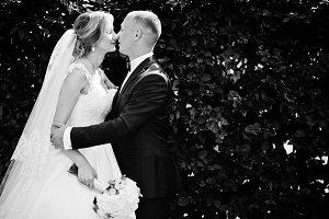 Fashionable wedding couple hugging a