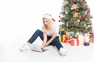 young woman in santa claus hat using