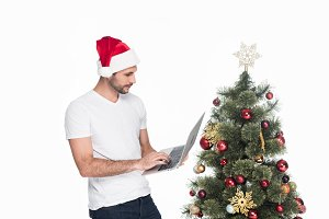 man in santa claus hat using laptop