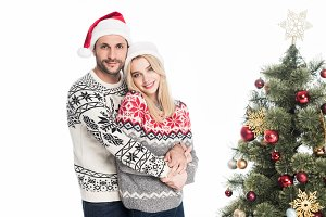 young couple in santa claus hats hug