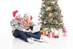 smiling couple in santa claus hats w