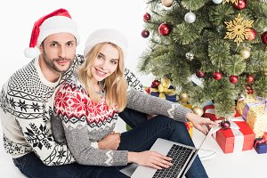 young couple in santa claus hats wit
