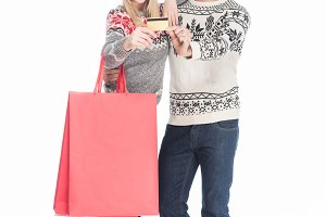 couple in santa claus hats with shop