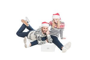 young couple in sweaters and santa c