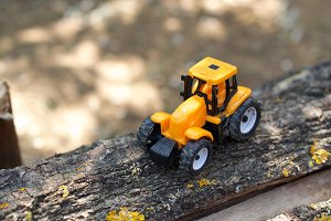 Yellow tractor toy on the wood