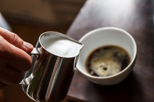 man pouring into a cup of coffee wit