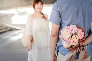 A man holding bouquet of flowers