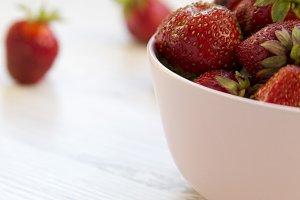Fresh ripe strawberries in a pink