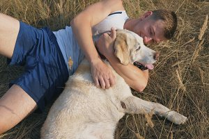 Young man lies on meadow and plays