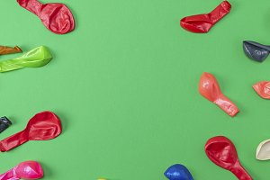 colorful deflated balloons on a gree