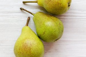 Fresh pears on a white wooden table