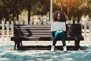 Curly girl with the laptop in a park