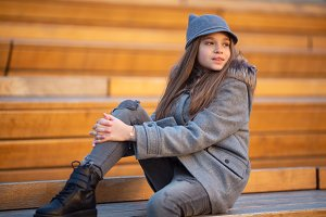 Photo of girl in gray coat sitting