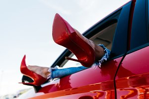 Photo of woman's legs in red shoes