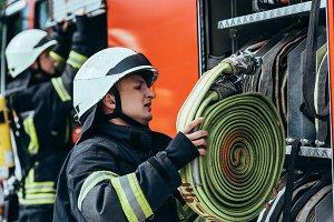 male firefighter in helmet putting w