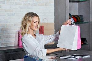 smiling female seller holding shoppi