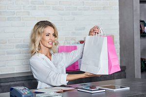 smiling young woman holding shopping