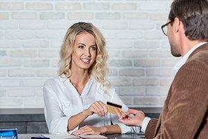 customer giving credit card to smili
