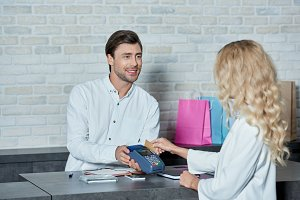 smiling man holding payment terminal