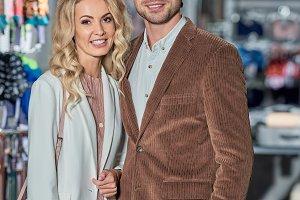 happy stylish couple holding shoppin