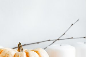 Small pumpkin and white candles