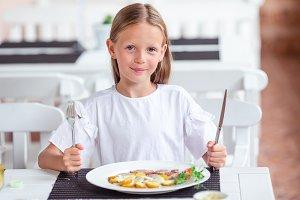 Adorable little girl having dinner a