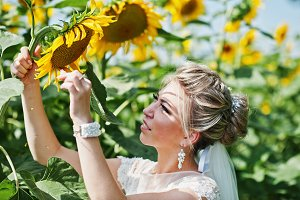 Blonde bride looking on sunflower at