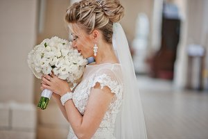 Blonde bride with wedding bouquet at