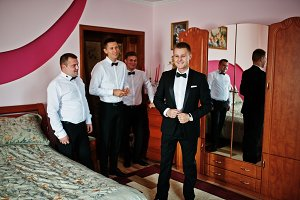 Groom wears on his room at morning w