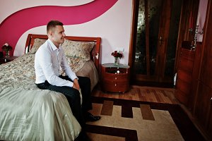 Groom sitting on bed at his room on