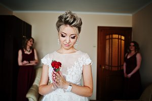 Blonde bride with buttonhole on hand