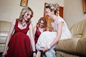 Bridesmaids helped wear shoes bride