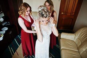 Bridesmaids helped wear bride dress