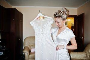 Blonde bride on silk robe with weddi