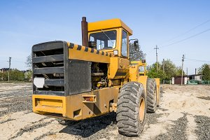 Yellow loader stands on a stone