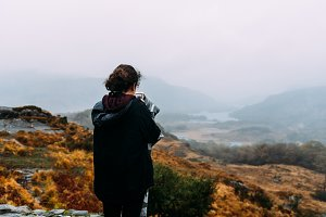 Young woman takes a picture in misty