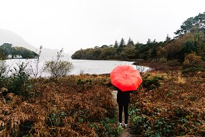 Woman with red umbrella by lake in