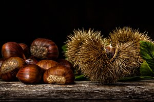Chestnuts and chestnut bur on wooden